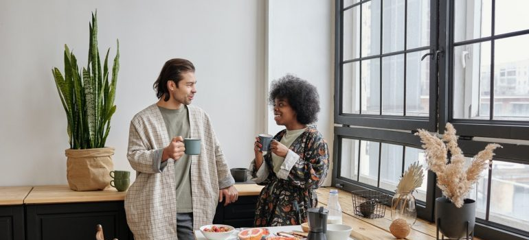A couple having a coffee and talking about room-by-room packing