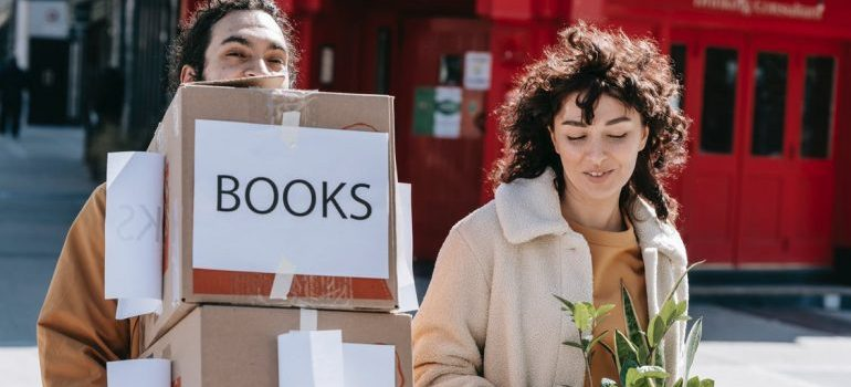 A man and a woman carrying boxes