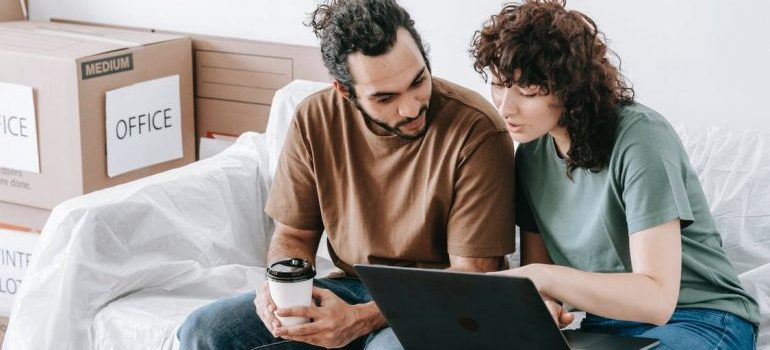 A man and a woman looking at the laptop screen