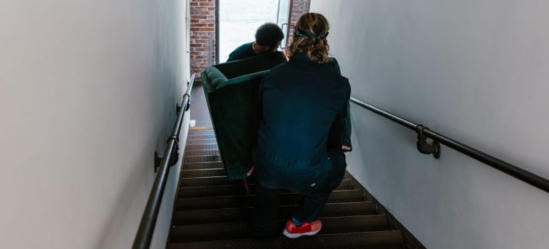 two people moving a sofa down the stairs