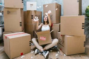 A woman having fun packing for a last-minute move.