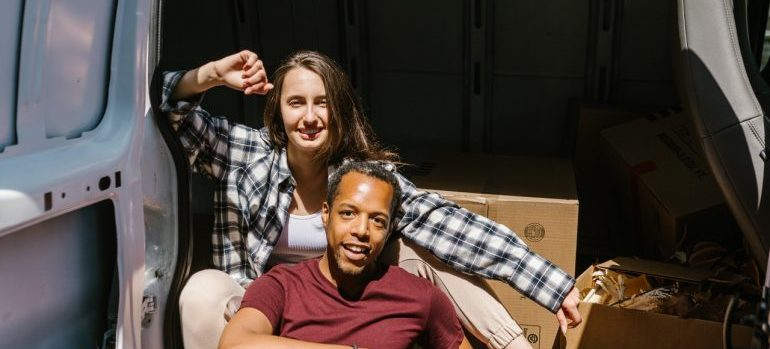 man and women by moving van following summertime relocation guide