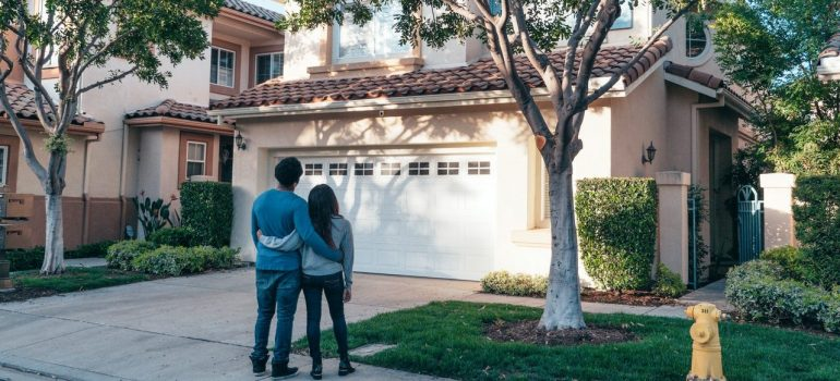 a couple looking at their new home from the driveway