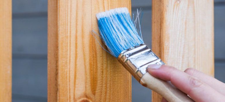 a person painting a wooden plank with a brush as you should when decorating your new home in Milwaukee