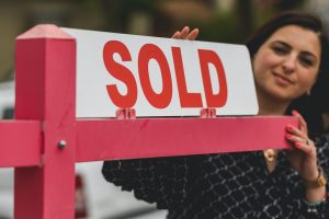 """a woman standing behind a """"sold"""" sign"""