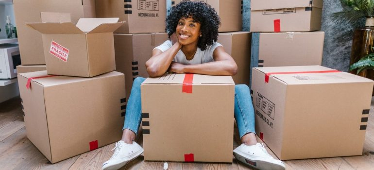 a woman smiling while sitting in front of packed cardboard boxes she prepared for moving to Frankfort