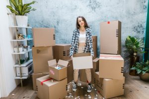 a woman standing in between boxes while holding one cardboard box