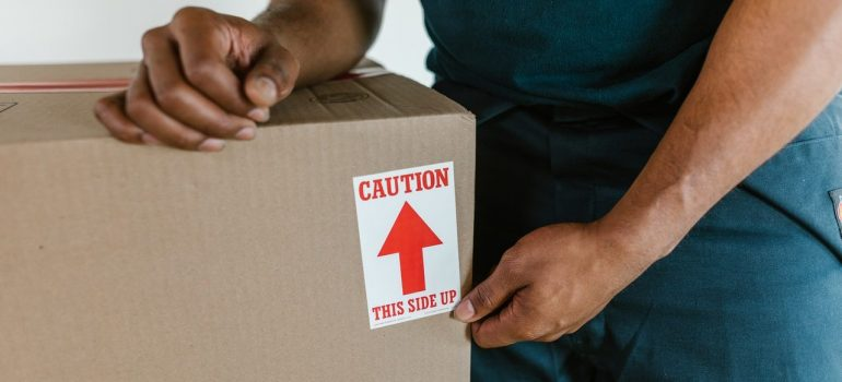 a movers holding onto a box with a label