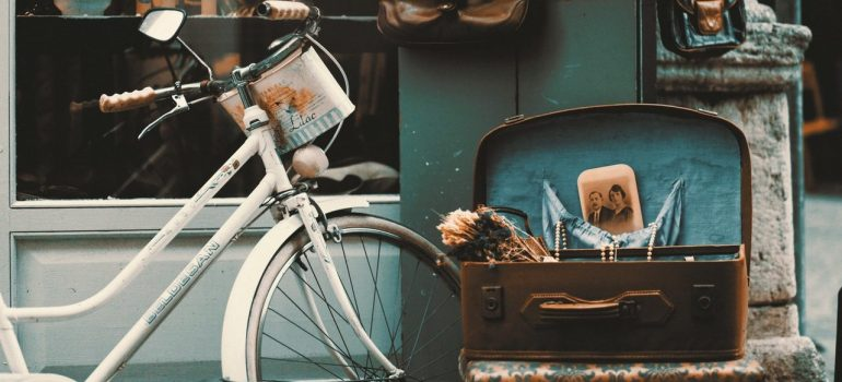 a bike near an old suitcase with old photographs inside it